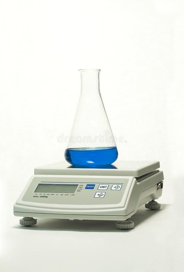 Produtos vidreiros de laboratório na escala fotos de stock