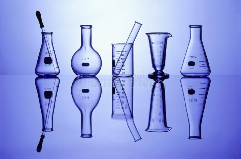 Produtos vidreiros de laboratório no azul fotografia de stock