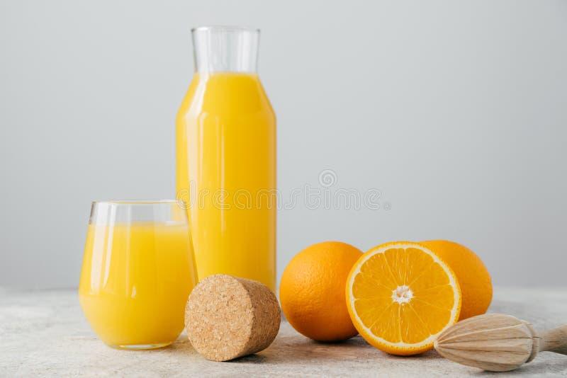 Produtos vidreiros do suco de laranja fresco, do fruto maduro e do espremedor de frutas de madeira contra o fundo branco Fatia de imagem de stock