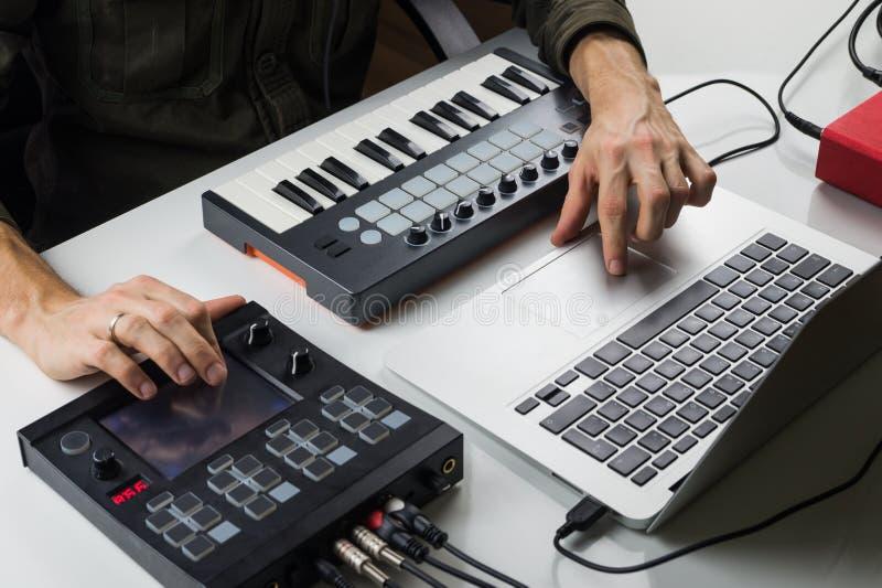 Produzieren der elektronischen Musik auf Laptop mit tragbarer Midi-Tastatur und elektronischen Effektprozessoren lizenzfreies stockfoto