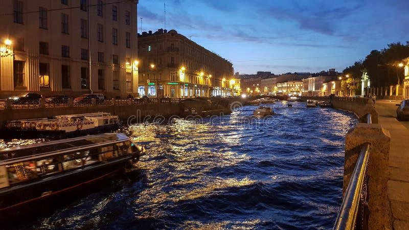 Produzindo a ponte do palácio em St Petersburg durante as noites brancas Vista de Neva River à ponte aumentada, ao Admiralty e ao foto de stock royalty free