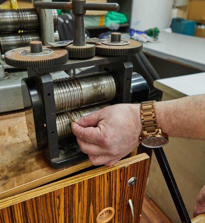 Produzione dei gioielli Riciclaggio delle materie prime Mestiere dei gioielli sulla macchina della laminazione immagine stock