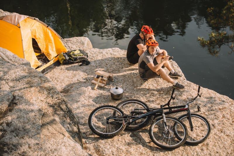 proeffietsers die dichtbij tent en cycli op rotsachtige klip rusten stock fotografie