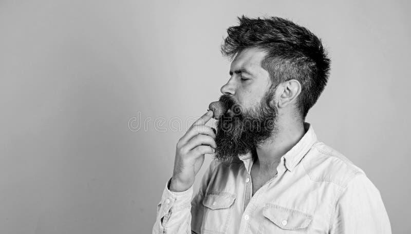 Proeft zo de zomer Mensen knappe hipster met lange baard die aardbei eten Hipster geniet van sappig rijp rood royalty-vrije stock afbeeldingen