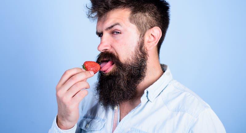 Proeft zo de zomer Mensen knappe sexy hipster met lange baard die aardbeitong likken Hipster geniet van sappige rijp stock foto