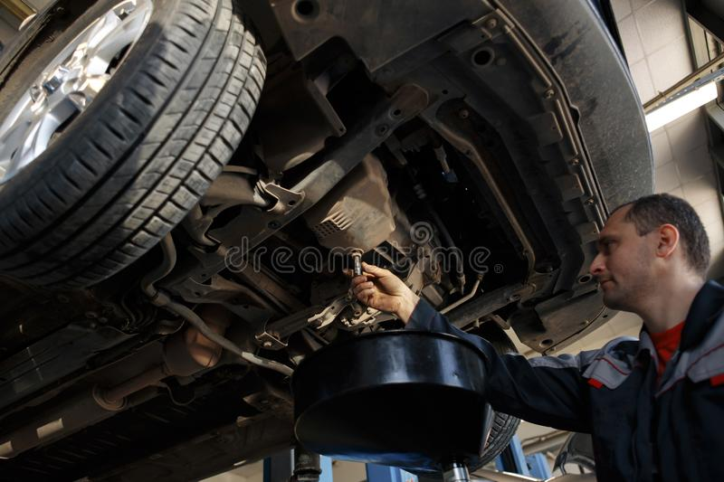 Profecional car mechanic changing motor oil in automobile engine at maintenance repair service station in a car workshop. Profecional car mechanic changing motor stock photo