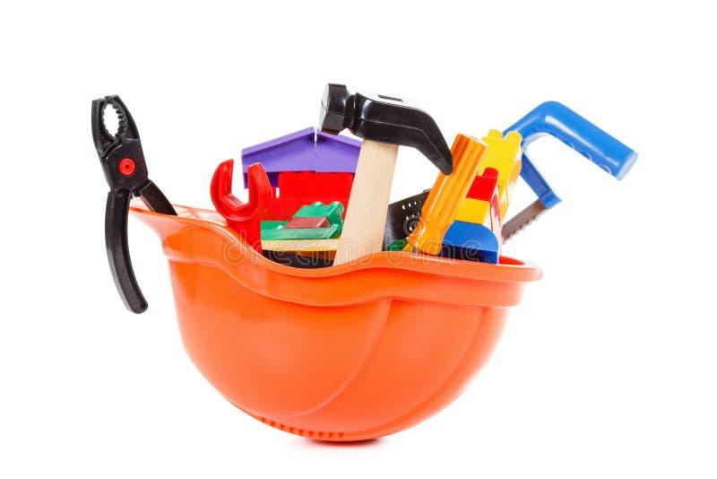 Profesión del constructor del concepto, casco protector y juguete aislados en blanco fotografía de archivo libre de regalías