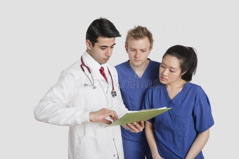 Profesional de la atención sanitaria tres que discute informe médico sobre fondo gris imagen de archivo libre de regalías