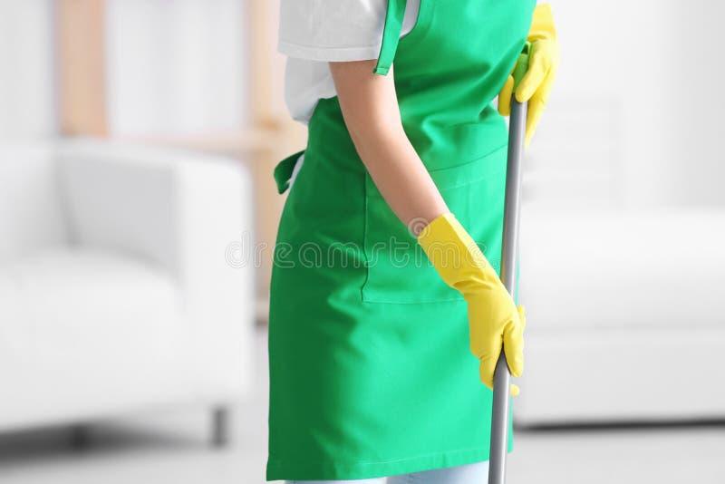 Profesional del servicio de la limpieza con la fregona dentro foto de archivo libre de regalías