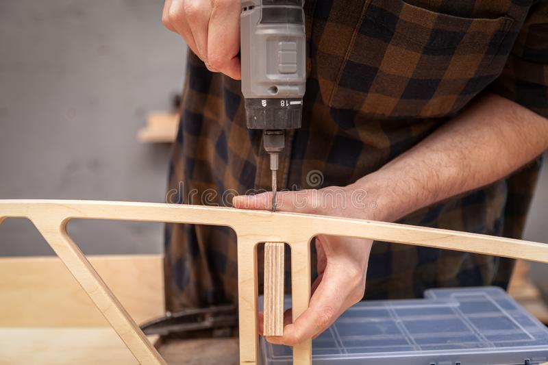 Handicraft Carpentry. Profesional drilling wood on vertical drill machine. Close up of a metal drill making holes in the wood stock image