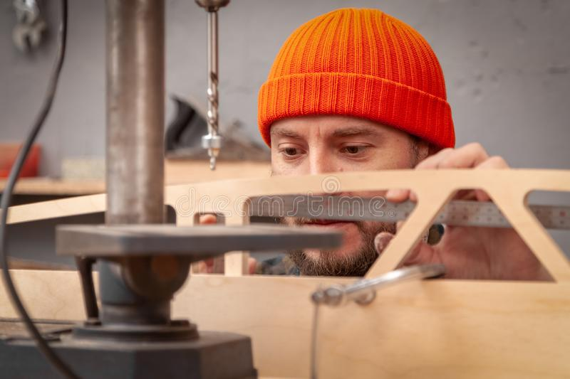 Construction Worker. Profesional drilling wood on vertical drill machine. Close up of a metal drill making holes in the wood stock images
