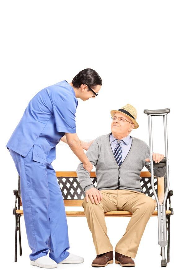 Profesional masculino de la atención sanitaria que ayuda a un caballero mayor asentado fotografía de archivo
