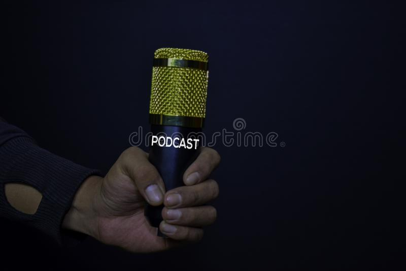 Profesional Microphone on hands isolated black background. Podcast Concept royalty free stock images