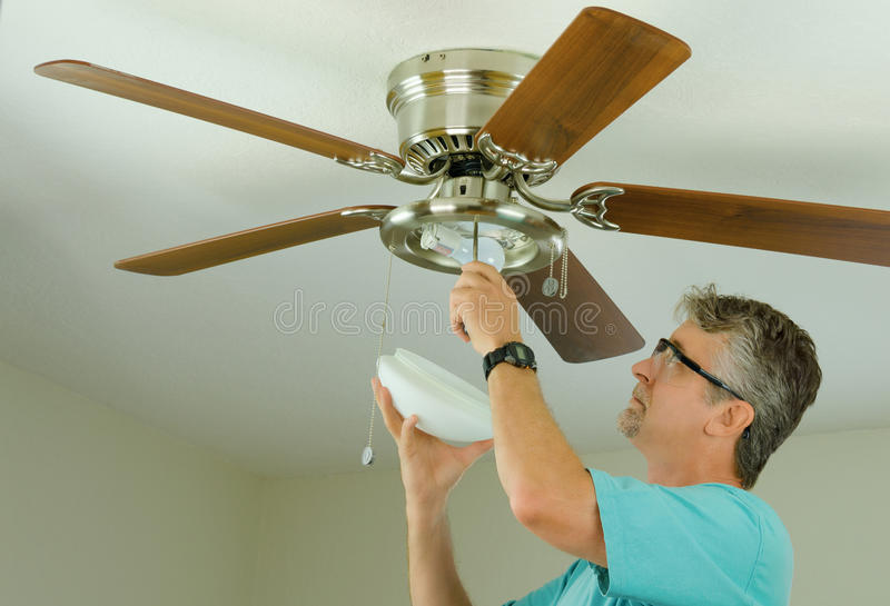 Profesional o dueño casero de DIY que hace el trabajo de la reparación de la fan de techo imagen de archivo