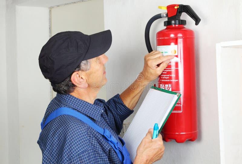Profesional que comprueba el extintor en llamas imagen de archivo