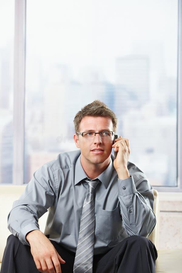 Profesional que escucha el phonecall en el sofá fotos de archivo libres de regalías