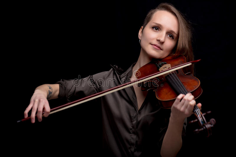 Profesional violinist on a black background. Passionate violinist playing her classical music instrument on a black background and enjoying stock images