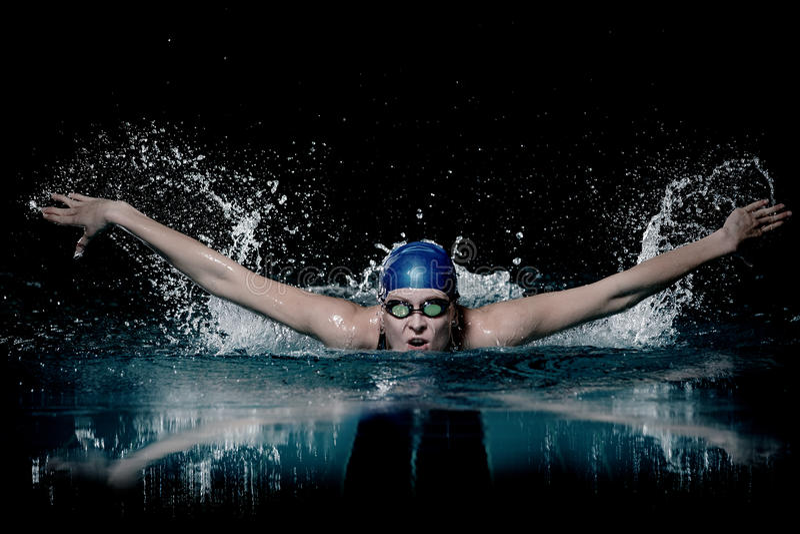 Profesional woman swimmer swim using breaststroke technique on the dark background stock photo