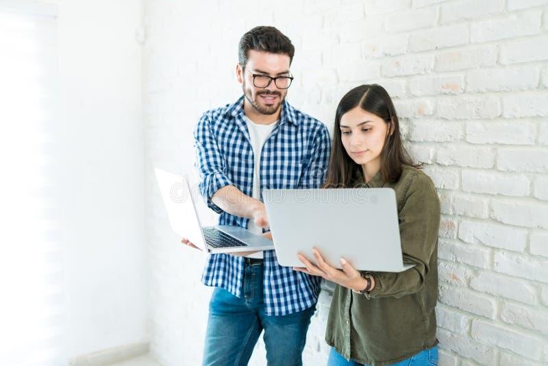 Profesionales con los ordenadores portátiles contra la pared en oficina foto de archivo