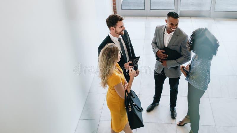 Profesionales corporativos que tienen reunión casual en pasillo de la oficina imágenes de archivo libres de regalías