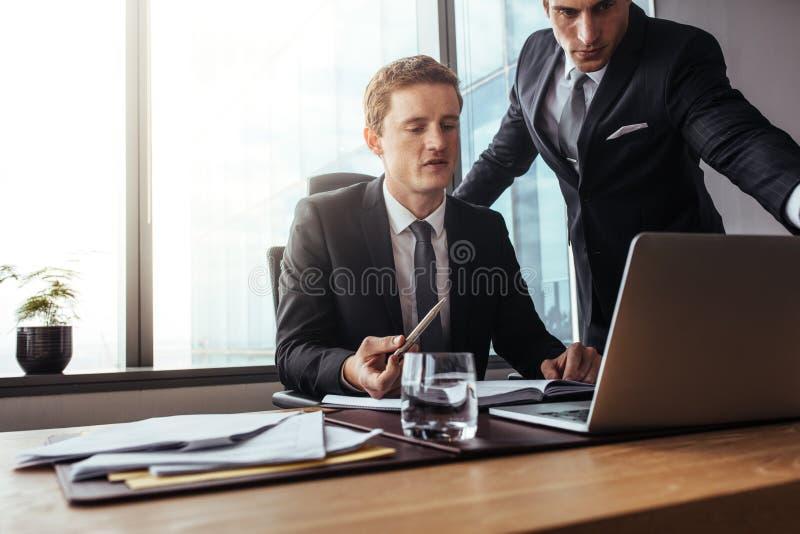 Profesionales corporativos que trabajan junto en el ordenador portátil imagen de archivo libre de regalías
