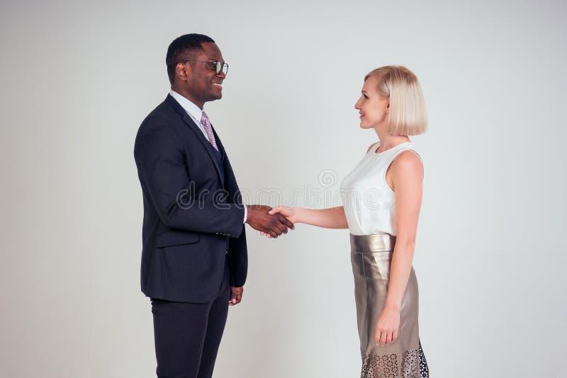 Profesionales de negocios que trabajan en estudio de fondo blanco. Hombre afroamericano y mujer caucásica fotos de archivo