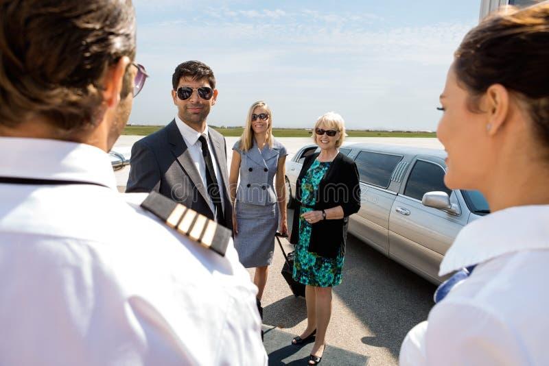 Profesionales del negocio que saludan al piloto And foto de archivo