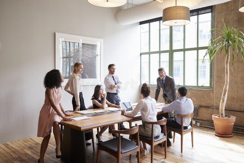 Profesionales jovenes alrededor de una tabla en una reunión de negocios imagenes de archivo