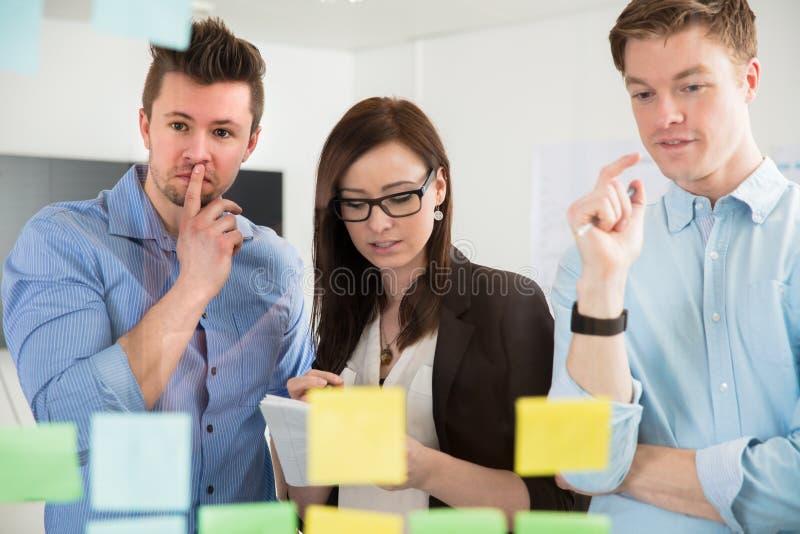 Profesionales que planean estrategias en notas adhesivas en oficina foto de archivo libre de regalías