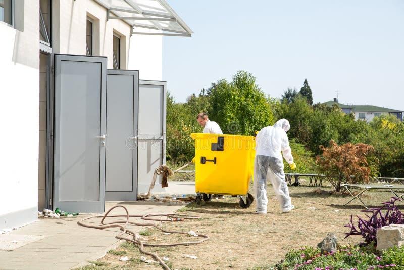 Profesjonaliści czyści toaletę w improwizującym obozie uchodźców obrazy stock