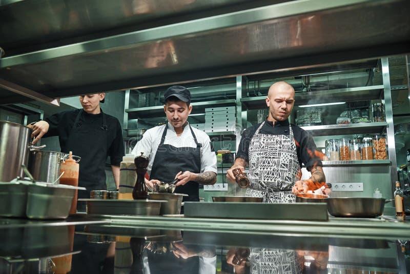 profesjonalista drużyna Młody brutalny szef kuchni w mundurze flambeing w fachowej kuchni fotografia royalty free