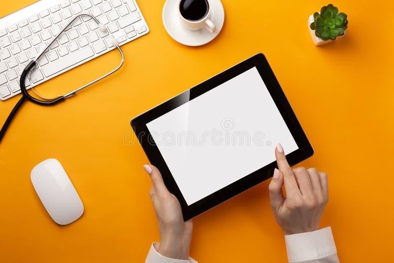 Profesjonalista lekarka pisze książeczkach zdrowich w cyfrowej pastylce z stetoskopem, klawiaturą, filiżanką i myszą, zdjęcia stock
