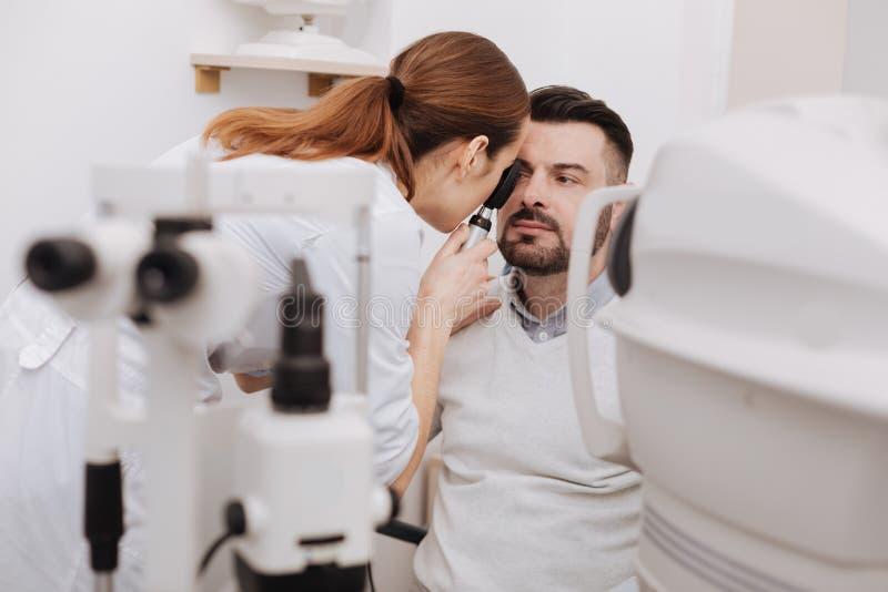Profesjonalisty doświadczony optometrist używa oftalmoskop obrazy stock