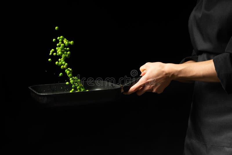 Profesjonalisty kucharz szefa kuchni narządzania naczynie z zielonymi grochami w niecce Na czarnym tle menu, przepis książka, zdr obraz stock