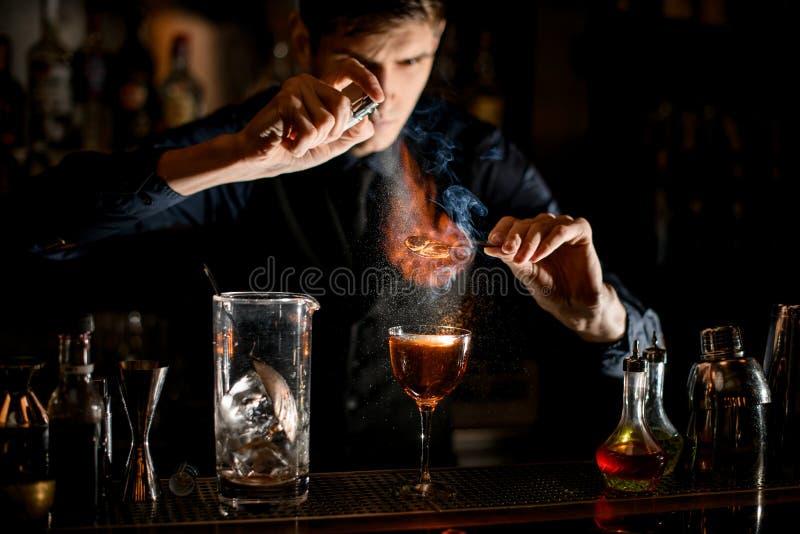 Profesjonalny barman trzyma pęsety z kawałkiem cytrusu na szkle i posypuje je posypką fotografia stock