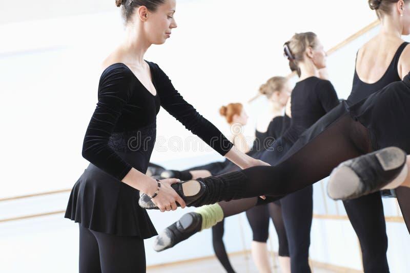 Profesor Adjusting Foot Positions del ballet de bailarinas imagen de archivo