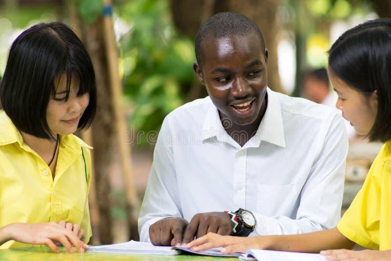 Profesor africano que enseña al estudiante asiático sobre idiomas extranjeros imágenes de archivo libres de regalías