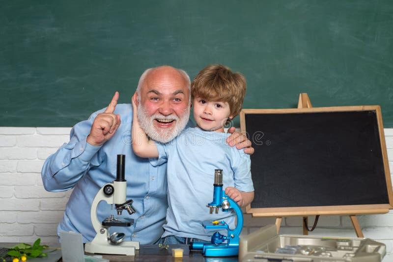 Profesor amistoso en sala de clase cerca del escritorio de la pizarra Microscopio del laboratorio y ciencia de la biología para l fotografía de archivo libre de regalías