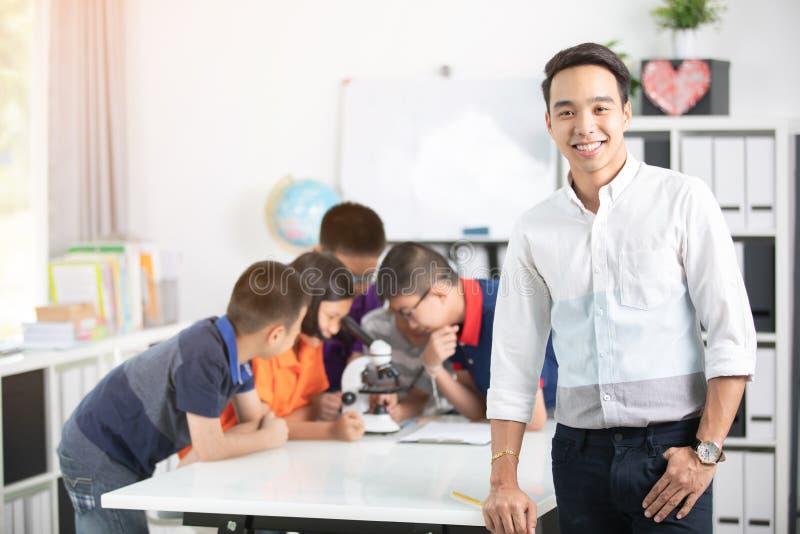 Profesor asiático que se amplía al estudiante en clase de Biología con el microsc imagen de archivo libre de regalías