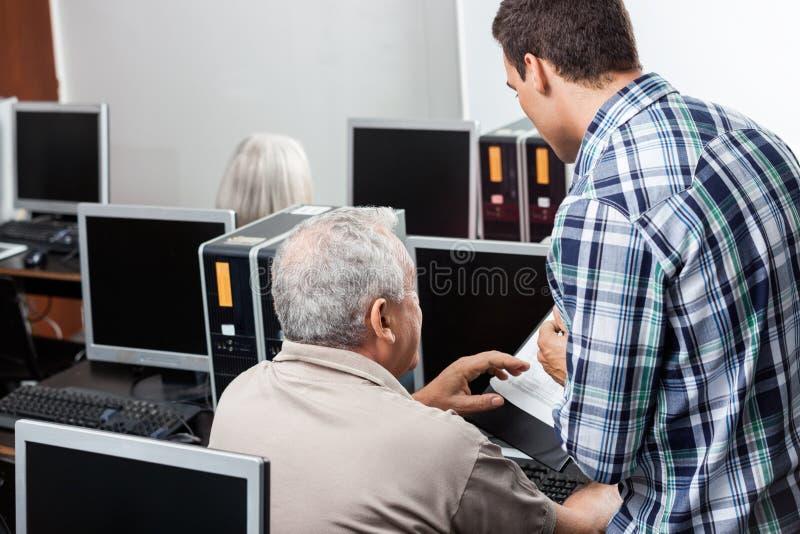 Profesor Assisting Senior Man al usar el ordenador en la sala de clase fotos de archivo
