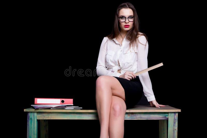 Profesor atractivo que presenta en el escritorio en estudio en fondo negro imagen de archivo