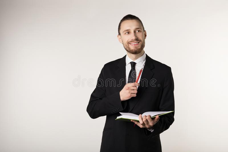 Profesor barbudo atractivo joven en traje y cuaderno negros de la tenencia del lazo y pluma en manos imágenes de archivo libres de regalías