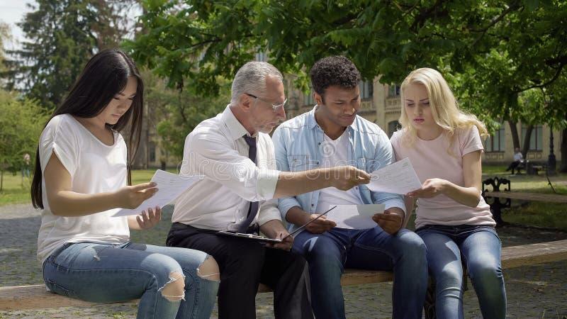 Profesor calificado que da pruebas a los estudiantes multirraciales en parque cerca de universidad fotos de archivo