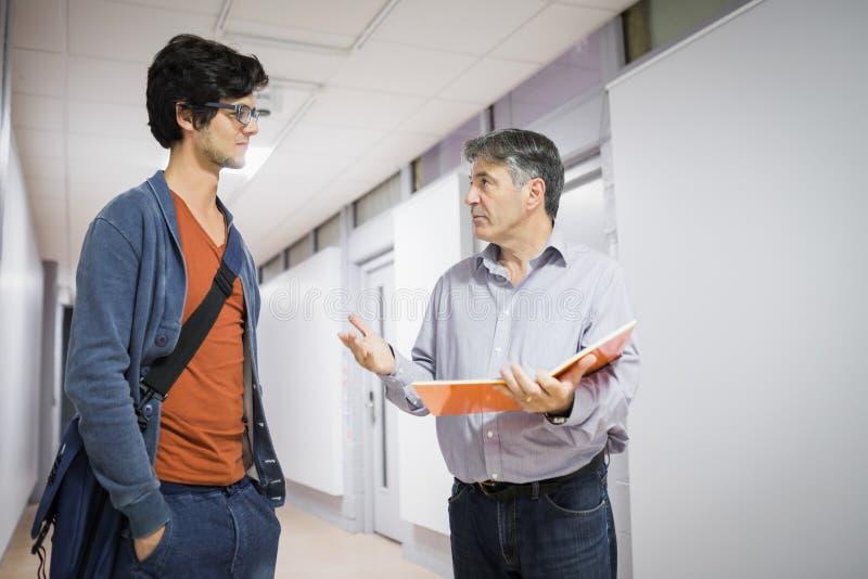 Profesor con el cuaderno que habla con un estudiante fotos de archivo libres de regalías
