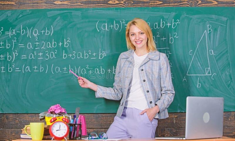 profesor con el despertador en la pizarra Tiempo Estudio y educaci?n Escuela moderna D?a del conocimiento Mujer en sala de clase imagen de archivo