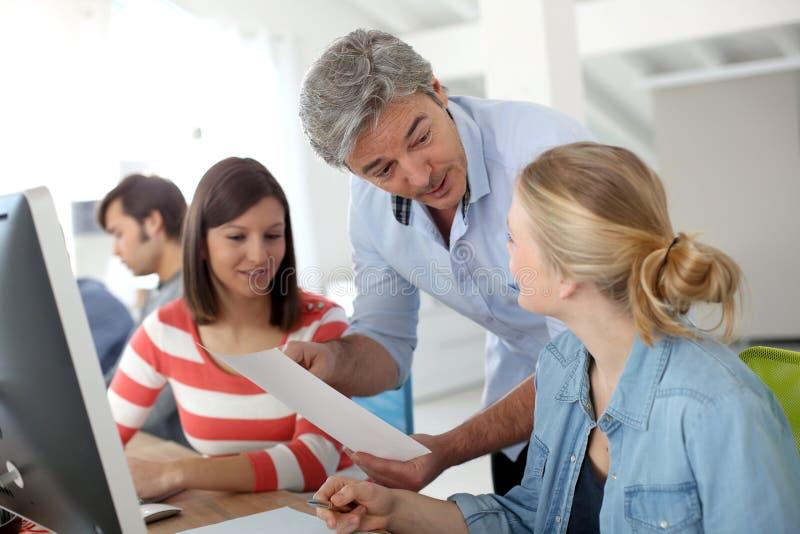 Profesor con el grupo de estudiantes en sala de clase foto de archivo libre de regalías