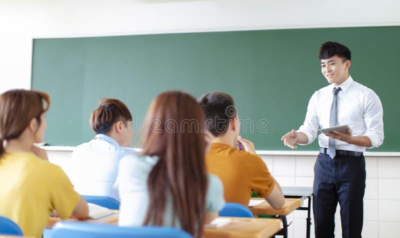 Profesor con el grupo de estudiantes universitarios en sala de clase imagen de archivo libre de regalías