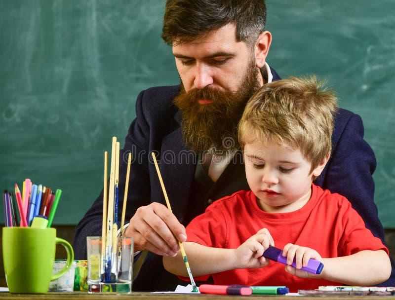 Profesor con la barba, padre y pequeño hijo en sala de clase mientras que dibuja, creando, pizarra en fondo Talento y fotos de archivo