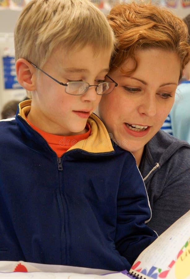 Profesor con la lectura del niño fotografía de archivo libre de regalías