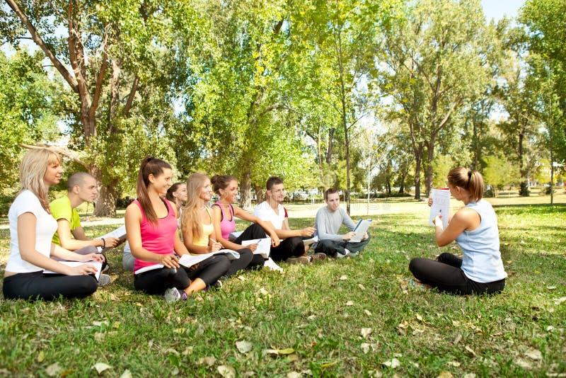 Profesor con los estudiantes en parque fotografía de archivo